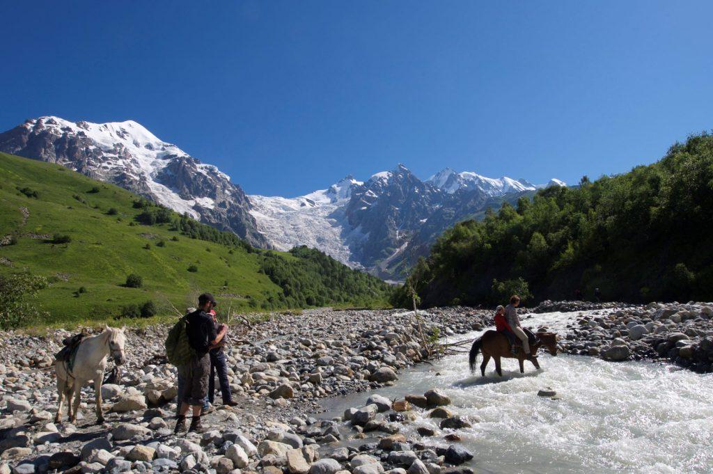 Flussüberquerung mit dem Adischi-Gletscher im Hintergrund